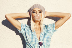 Trendy beautiful blonde model and Blow bubblegum royalty free stock images