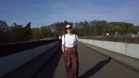 Trendy woman in velvet pants walking on bridge. Trendy beautiful caucasian woman walking on bridge. Attractive glamorous lady, model in pink velvet pants stock video footage