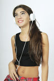 Trendy beautiful young girl listening to music with headphones. Royalty Free Stock Photos