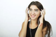 Trendy beautiful young girl listening to music with headphones. Stock Image