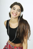 Trendy beautiful young girl listening to music with headphones. Stock Photos