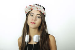 Trendy beautiful young girl listening to music with headphones. Royalty Free Stock Images