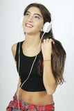 Trendy beautiful young girl listening to music with headphones. Royalty Free Stock Photography