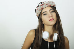 Trendy beautiful young girl listening to music with headphones. Stock Photo