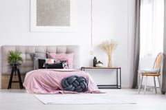 Trendy bedroom with orange chair. Black braided pillow and pink overlay on king-size bed in trendy bedroom with orange chair and copper lamp royalty free stock image