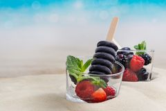 Trendy black charcoal ice cream popsicles. In glass cups on sandy beach. Copy space royalty free stock images