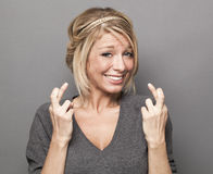 Trendy blond girl trusting faith in crossing her fingers tight Stock Images