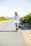 Trendy blonde with sunglasses hitchhiking Stock Image