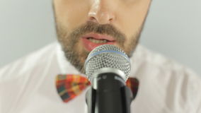 Trendy blue-eyed man with a mustache and beard. Trendy blue-eyed man with mustache and beard sings into microphone stock footage