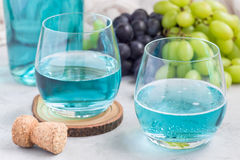 Trendy blue moscato wine in glass and in bottle, green and red grape on background, horizontal Stock Photos
