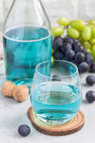 Trendy blue moscato wine in glass and in bottle, green and red grape on background, vertical Royalty Free Stock Image