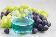 Trendy blue moscato wine in a glass, green and red grape on background, horizontal Stock Images