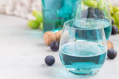 Trendy blue moscato wine in glass, green and red grape on background, horizontal Royalty Free Stock Photo