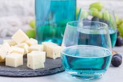Trendy blue moscato wine in a glass served with a cheese plate, green and red grape on background, horizontal Stock Photography