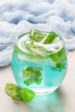 Trendy blue moscato wine in glass, served with mint ice cubes, vertical. Trendy blue moscato wine in a glass, served with mint ice cubes, vertical Royalty Free Stock Image
