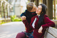 Trendy boy kissing his stylish mother outdoor. Stylish trendy boy and women or son with mother posing outdoor Royalty Free Stock Images