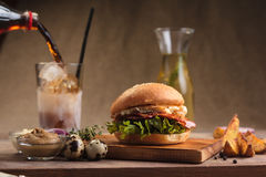 Trendy breakfast burger with ham and eggs. Concept: restaurant menus, healthy eating, homemade, gourmands, gluttony. Trendy breakfast burger with ham and eggs Stock Images