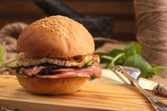 Trendy breakfast burger with ham and eggs. Concept: restaurant menus, healthy eating, homemade, gourmands, gluttony. Trendy breakfast burger with ham and eggs Stock Photography