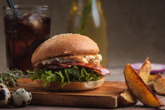 Trendy breakfast burger with ham and eggs. Concept: restaurant menus, healthy eating, homemade, gourmands, gluttony. Trendy breakfast burger with ham and eggs Royalty Free Stock Photos