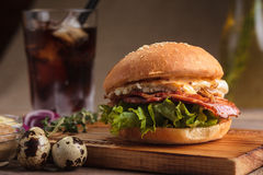 Trendy breakfast burger with ham and eggs. Concept: restaurant menus, healthy eating, homemade, gourmands, gluttony. Trendy breakfast burger with ham and eggs Stock Image