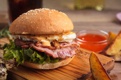 Trendy breakfast burger with ham and eggs. Concept: restaurant menus, healthy eating, homemade, gourmands, gluttony. Trendy breakfast burger with ham and eggs Royalty Free Stock Photography