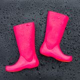 Trendy bright pink rubber boots on black wet surface covered with raindrops. stock images