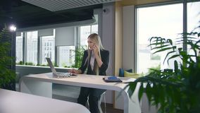 Trendy business woman watching laptop and speaking on phone. Stylish young blond woman working in office at table. Stylish young blond woman working in office at stock footage