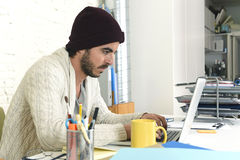 Trendy businessman in cool hipster beanie with coffee working busy at modern home office with compute Stock Photography