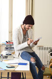 Trendy businessman in cool hipster beanie and informal look writing on pad working at home office Royalty Free Stock Photography