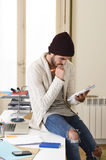 Trendy businessman in cool hipster beanie and informal look writing on pad working at home office Stock Photography