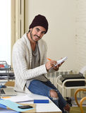Trendy businessman in cool hipster beanie and informal look writing on pad working at home office Stock Photo