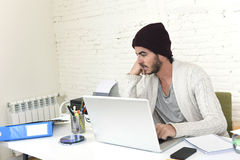 Trendy businessman in cool hipster beanie looking to laptop computer monitor analyzing project Royalty Free Stock Photos