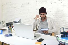 Trendy businessman in cool hipster beanie writing on pad working in at modern home office with computer Stock Photo