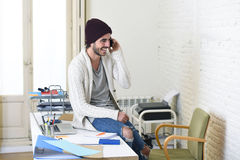 Trendy businessman hipster informal look smiling happy on mobile phone. Young trendy businessman in beanie and cool hipster informal look sitting on office desk Stock Photos