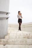 Trendy businesswoman messaging on smartphone. Trendy young businesswoman on a job break in modern corporate building stairs on a working day messaging on Royalty Free Stock Photos