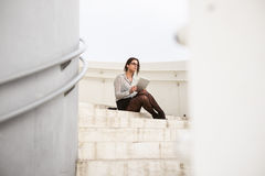 Trendy businesswoman using internet digital tablet. Trendy young businesswoman on a job break sitting in modern corporate building stairs on a working day using Stock Photo