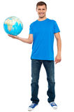 Trendy casual guy posing with a globe Royalty Free Stock Photos