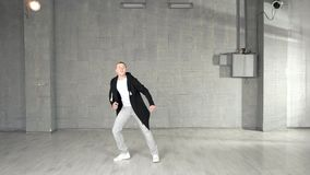 Trendy caucasian boy performing dance moves in studio. Young stylish man performing contemporary dance on grey background stock video