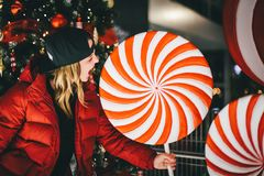 Trendy charming girl in red jacket wearing stylish cap biting gigantic lollipop royalty free stock photography