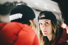 Girl in red jacket wearing stylish cap looking at false glass with pensive face stock images