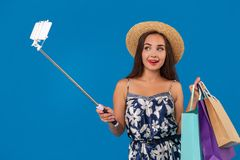 Young woman in casual clothes with shopping bags using selfie stick to take a self portrait on blue studio background. Trendy cheerful woman in casual clothes stock images