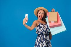 Young woman in casual clothes with shopping bags using selfie stick to take a self portrait on blue studio background. Trendy cheerful woman in casual clothes royalty free stock images