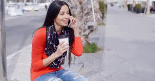 Trendy chic young woman listening to a mobile call. Trendy chic young woman sitting relaxing in an urban street listening to a call on her mobile phone with a stock footage