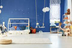 Trendy child room with table. Bed and blue wall Royalty Free Stock Images