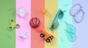 Trendy composition with earrings, sunglasses, beverage can, basketball ball, toy truck, gift box, flower and spinner. Trendy fashionable pastel composition with royalty free stock photo