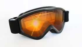 Trendy cool black ski goggles with the reflection of a beautiful yellow orange red sunset stock photos