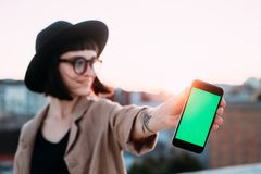 Trendy cool hipster girl holds chroma key phone. Beautiful young woman in fedora hat and hipster sunglasses, shows smartphone screen to camera with chroma key Stock Images