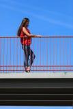 Trendy cool teenage girl on the urban bridge. Sporty style. Trendy cool teenage girl on the urban bridge. Copy space on blue sky. Summer Stock Image