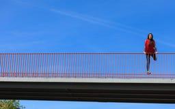 Trendy cool teenage girl on the urban bridge. Sporty style. Trendy cool teenage girl on the urban bridge. Copy space on blue sky. Summer Royalty Free Stock Photography