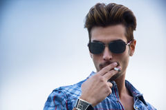 Trendy cool young man standing outside smoking Royalty Free Stock Photo